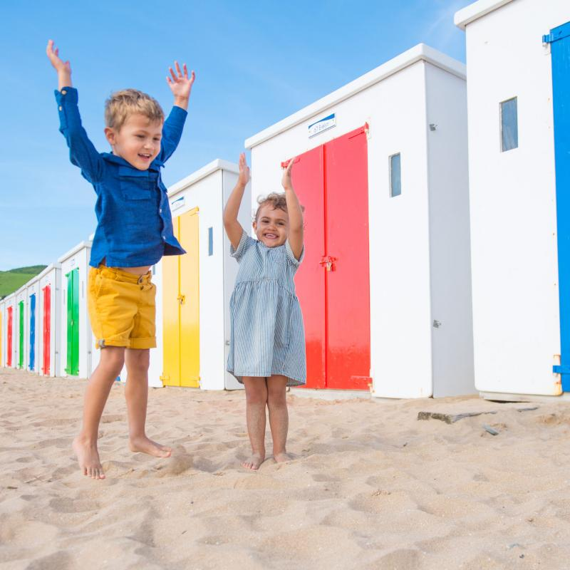 Children playing by beach huts in Woolacombe Devon