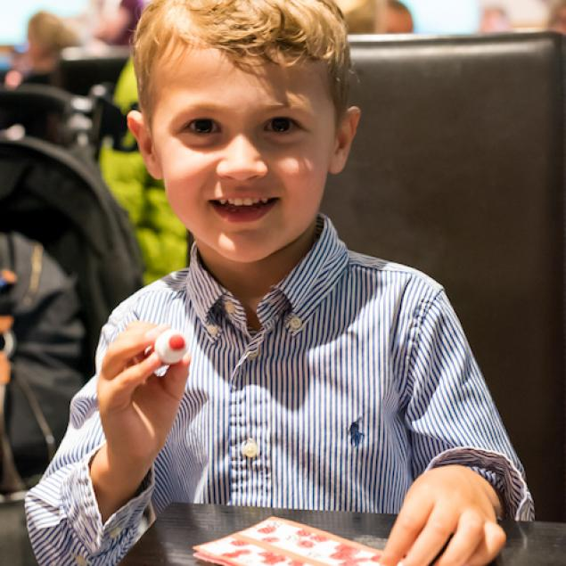 Young boy helps Mum and Dad play bingo at Woolacombe Sands Holiday Park